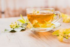 Cup of tea and linden on wooden background Royalty Free Stock Photos