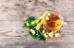 Cup of tea and linden on wooden background Royalty Free Stock Photo