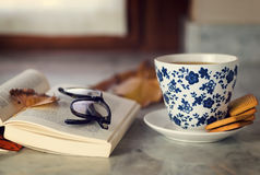 A cup of Green Tea on a marble table with an open book stock photo