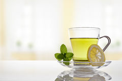 Cup of green tea with mint and lemon front view. Glass cup green tea with mint and lemon on a table in the living room. Horizontal composition. Front view Stock Image