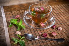 Cup of green tea with mint and roses Royalty Free Stock Images