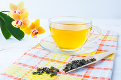 Cup of green tea on orange checkered napkin Stock Image