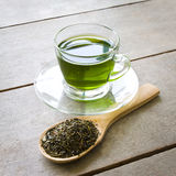 Green tea. Cup of green tea and spoon of dried green tea leaves on wooden background Stock Photos
