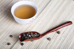 Cup of green tea and tea leaves spoon on a napkin from a bamboo Stock Photo