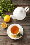 Cup with green tea and teapot on a grey wooden background Royalty Free Stock Photo
