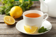 Cup with green tea and teapot on the grey wooden background Royalty Free Stock Photography