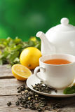 Cup with green tea and teapot on a grey wooden background Royalty Free Stock Image