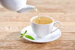 Cup with green tea and teapot on white wooden table background. Royalty Free Stock Photo