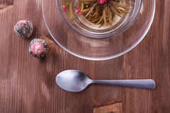Cup of green tea with teaspoon. Transparent cup of green tea with the teaspoon on the wooden table Royalty Free Stock Photo