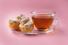 A cup of green tea and three profiteroles sprinkled with sugar powder on a pink background. stock images