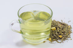Cup of green tea whit ginseng pieces. Cup of green tea leaves whit ginseng pieces on white background Stock Photography