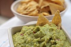 Cup of guacamole with blurred nachos in background Stock Photos
