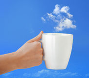 Cup in hand on the blue sky with cloud. Stock Images