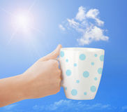 Cup in hand on the blue sky with cloud. Royalty Free Stock Photo
