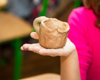 A cup in the hand of the child. Royalty Free Stock Photography
