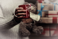 Cup in hand and stack gifts Stock Image