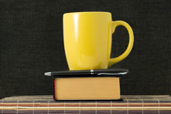 Cup, handle and book Stock Image