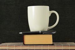 Cup, handle and book Royalty Free Stock Image