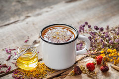 Cup of healthy daisy tea, honey and healing herbs on table. Royalty Free Stock Images