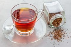 Cup of healthy herbal rooibos red tea in glass cup. And dry tea on background Royalty Free Stock Photo