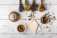 Cup of healthy tea, honey, healing herbs, herbal tea assortment and berries on table. Top view. Herbal medicine. Stock Photos