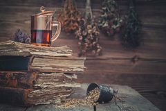 Cup of healthy tea, mortar of herbs and old books. Hanging bunches of medicinal herbs on background. Royalty Free Stock Images