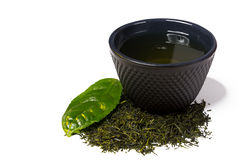 Cup and heap of green shincha tea with leaf. Royalty Free Stock Photo