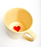 Cup with heart inside. Yellow cup with heart inside on a white background Stock Photography