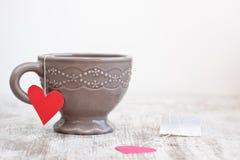 Cup with heart shaped tea bag Stock Photos
