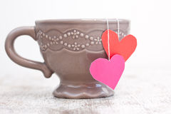 Cup with heart shaped tea bag Royalty Free Stock Images