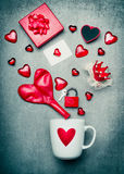 Cup with heart symbol and red Valentines day decoration with gift box, greeting card, lock and key, crown and balloon Stock Image