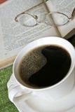 Cup heißer Kaffee, Buch im Hintergrund Lizenzfreie Stockbilder
