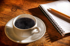 Cup heißer schwarzer Kaffee mit Dampf und Notizbuch Stockbild