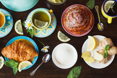 Cup of herb tea with lemon and mint leaves, ginger root and croissant Stock Image