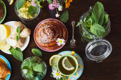 Cup of herb tea with lemon and mint leaves, ginger root and croissant Stock Photography