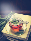 Cup of Herbal sage tea on a stack of books over rustic wooden background Royalty Free Stock Images