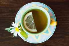 Cup of herbal tea with camomile and mint leaves on the wooden background Royalty Free Stock Image