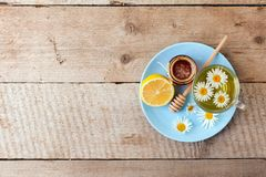 Cup of herbal tea with chamomile flowers, honey and lemon on a wooden table, rustic seasonal tea party royalty free stock photography