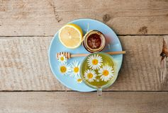 Cup of herbal tea with chamomile flowers, honey and lemon on a wooden table, rustic seasonal tea party royalty free stock image