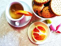 Cup of herbal tea,chocolate biscuit and half an orange served for breakfast stock photos