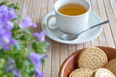 Cup herbal tea Cookies Flowers on bamboo tabletop Stock Image