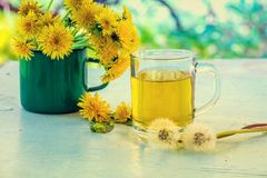 A cup of herbal tea. On a wooden table decorated with dandelion flowers royalty free stock image