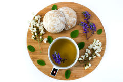 A cup of herbal tea and a honey cookies covered with white sugar glaze on a wooden sand board. Flowers and leaves white acacia stock photos