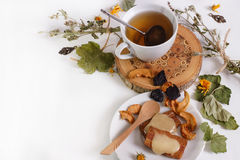 A cup of herbal tea with honey and dried fruits. A Cup of herbal tea with honey and dried fruit on a white table Royalty Free Stock Images