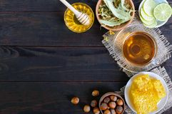 A cup of herbal tea, honey, honeycomb, hazelnuts on a dark wooden background Royalty Free Stock Images