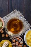 A cup of herbal tea, honey, honeycomb, hazelnuts on a dark wooden background. Royalty Free Stock Images