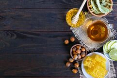 A cup of herbal tea, honey, honeycomb, hazelnuts on a dark wooden background. Royalty Free Stock Photos
