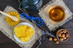 A cup of herbal tea, honey, honeycomb, hazelnuts on a dark wooden background. Stock Photo