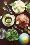 Cup of herbal tea with lemon and mint leaves, ginger root and baked good Stock Photo