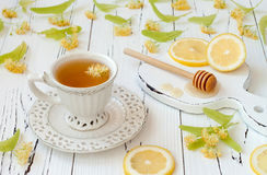 Cup of herbal tea with linden flowers, lemon and honey on a old wooden background. Stock Image
